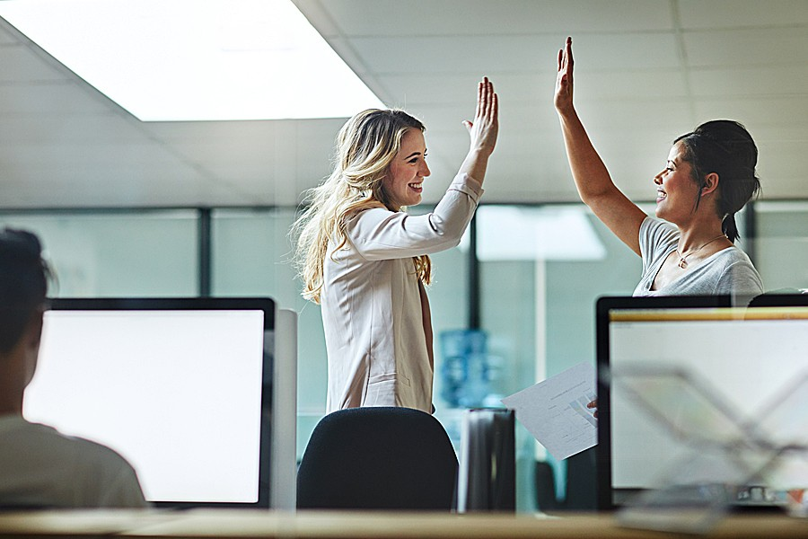 Two businesswomen high five in the office.