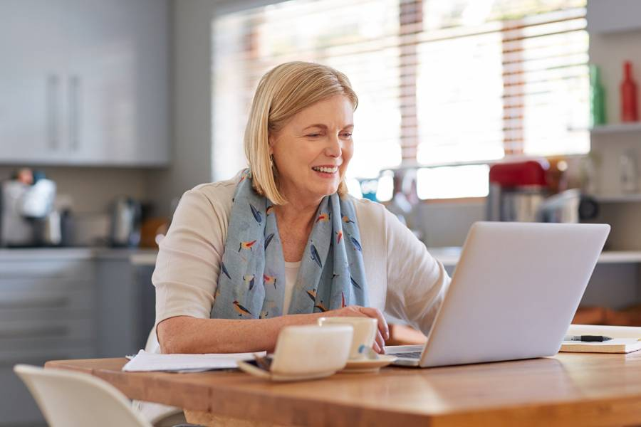Middle-aged woman at home checking her finances on a laptop