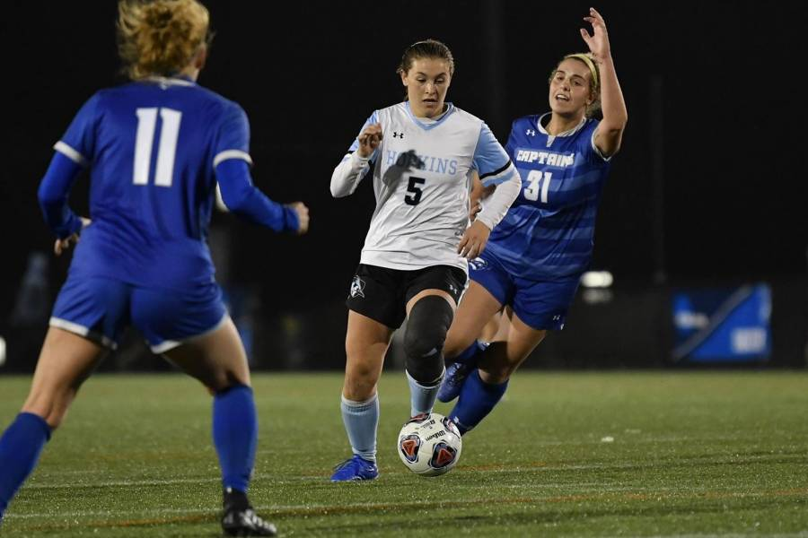 JHU soccer player dribbles through defenders