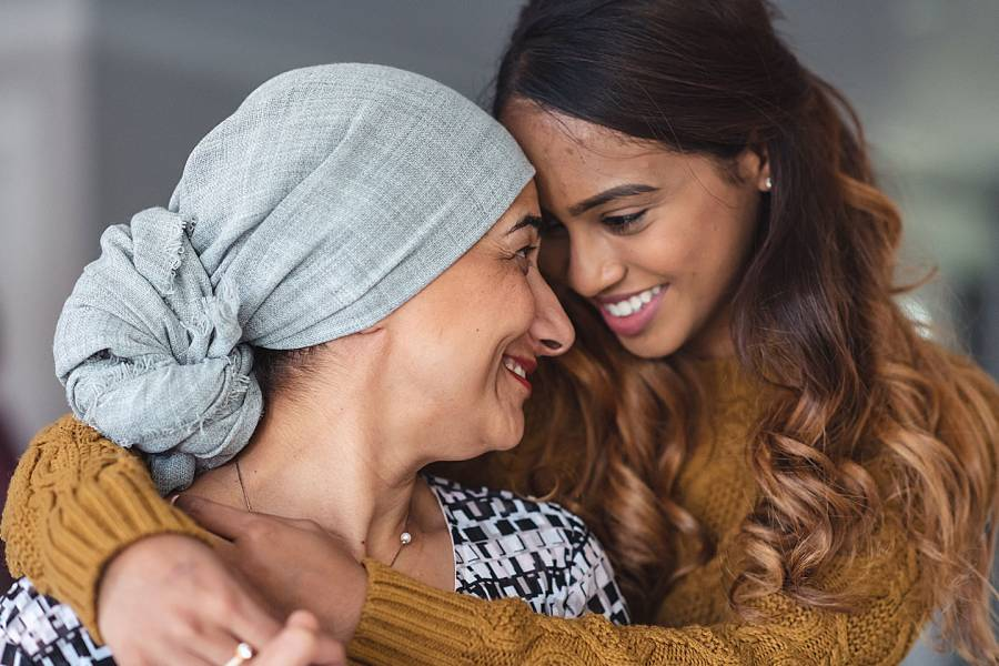 Two smiling women, one of them wearing a turban because of hair loss caused by her cancer treatment