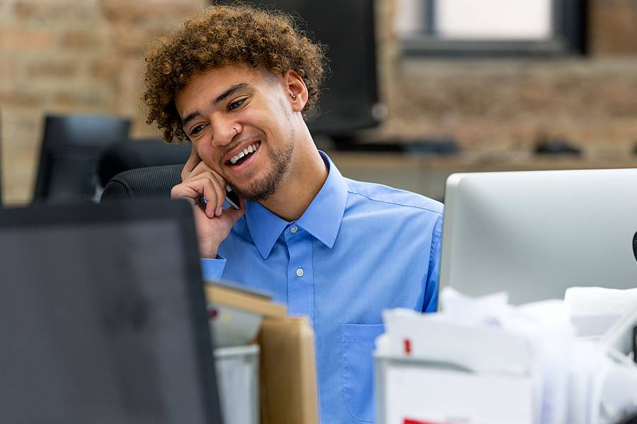Young man working in office surrounded by to monitors and many files