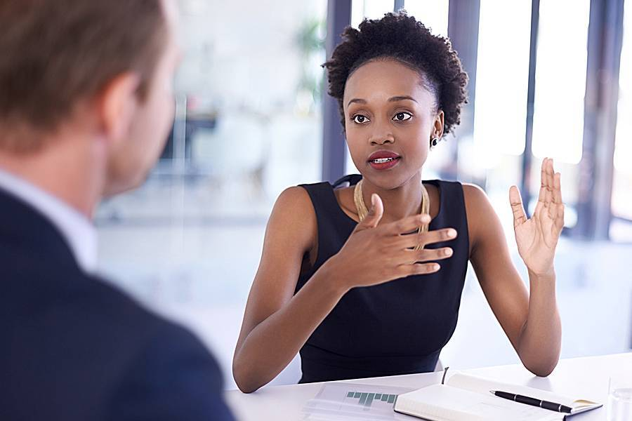 Woman at desk talking with colleague