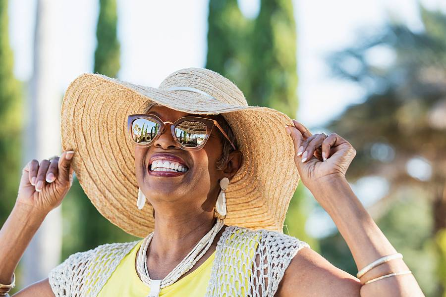 Smiling woman in big straw hat and sunglasses