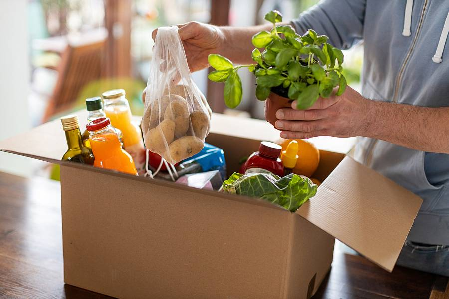 Closeup of man's hands unpacking a box of healthy groceries