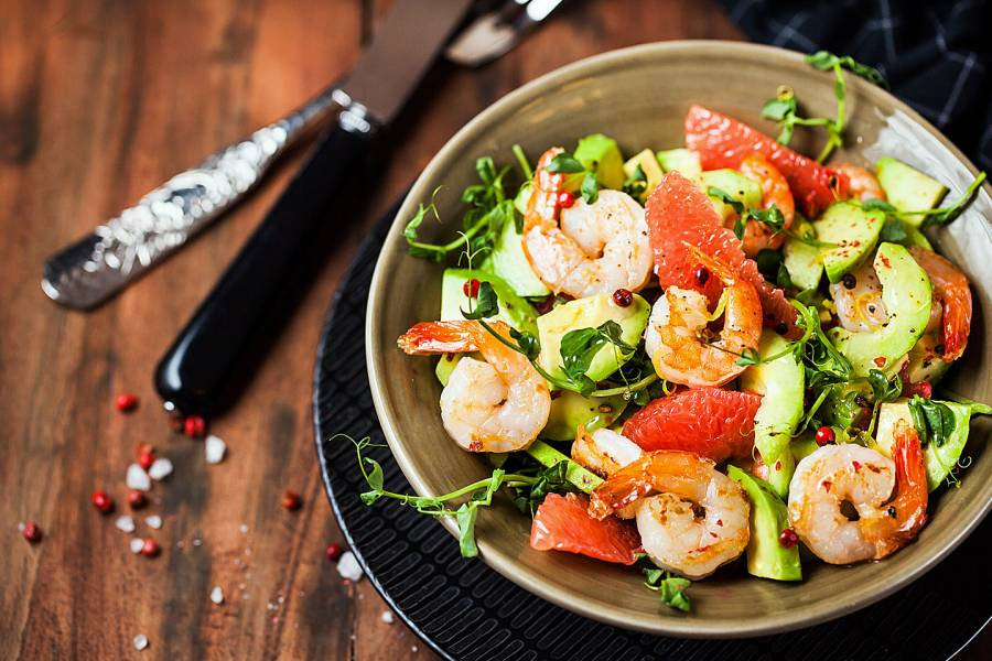 Shrimp, grapefruit, avocado, and greens in a salad bowl