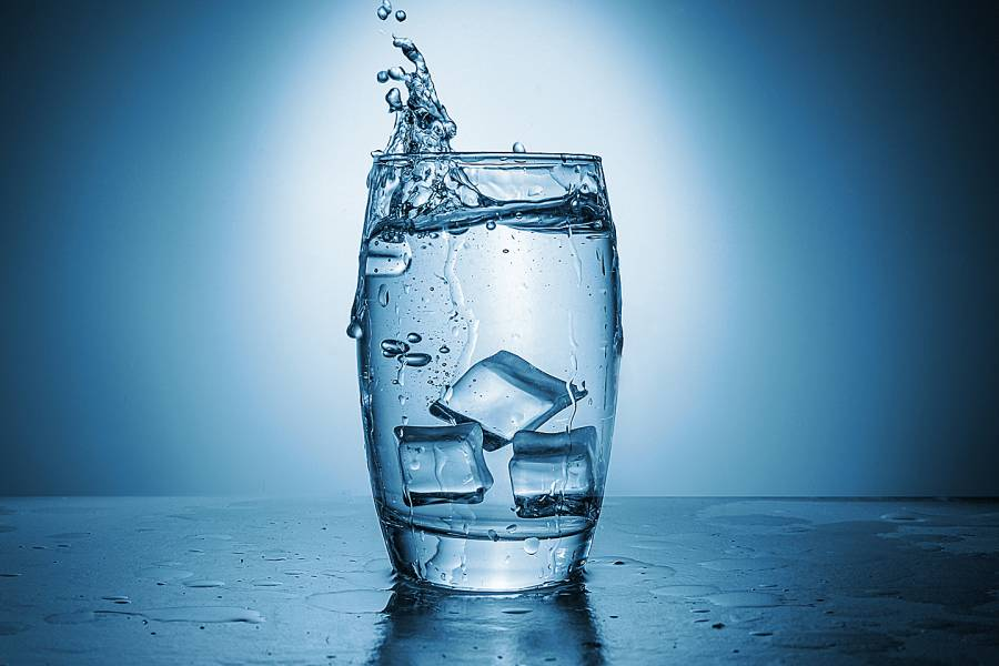 Water splashes out of a glass as ice cubes are dropped into it