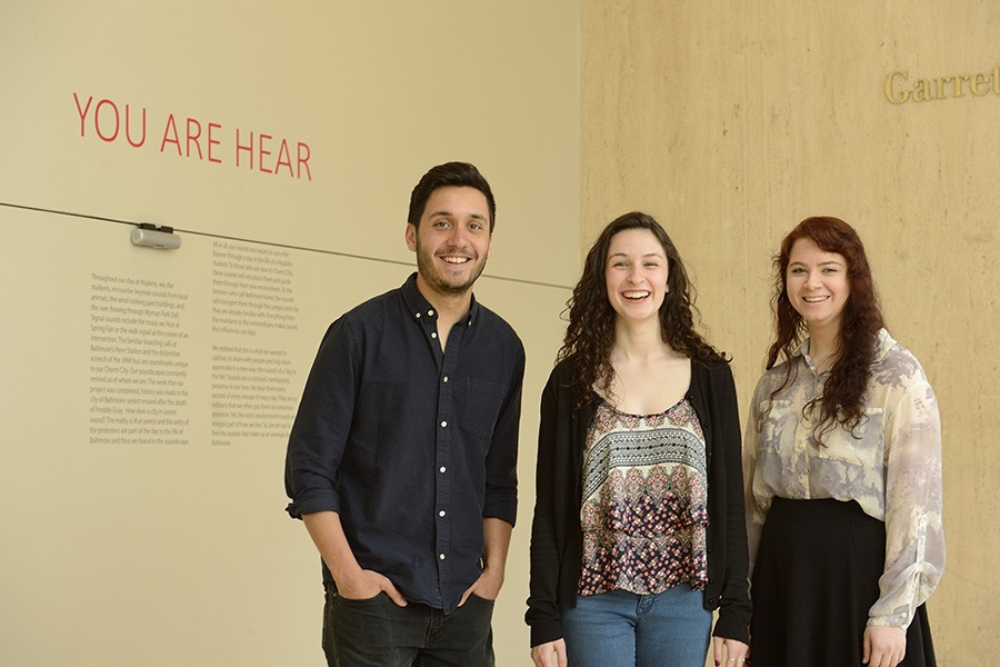 Three students pose in from of 'Your Are Hear' exhibition title in red letters on wall