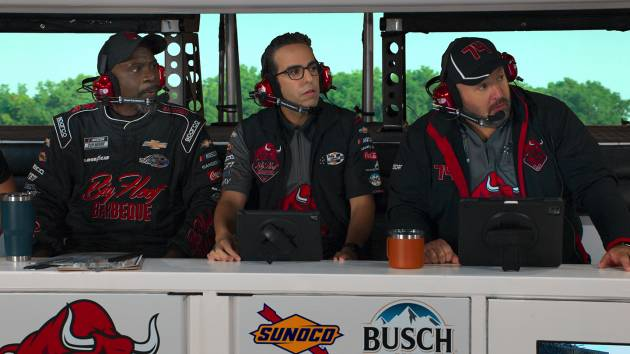 Dan Ahdoot (center) in a scene with actors Gary Anthony Williams (left) and Kevin James. The actors are wearing headsets and wearing racing gear.