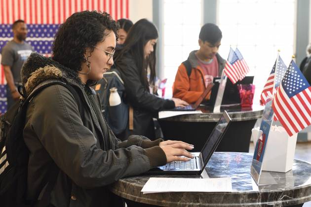 Students type on laptops next to American flags and bunting