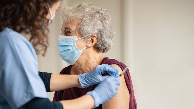 A vaccine is administered to an older woman