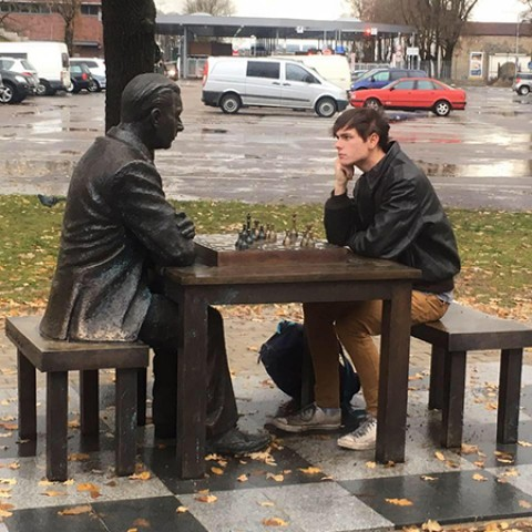 Ian Markham sits at an outdoor table playing chess against a statue